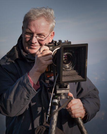 Während wir am Gipfel des Schafbergs auf den Sonnenuntergang warten, gelingt mir ein Schnappschuss von meinem Mann mit seiner Arca Swiss Fachkamera.